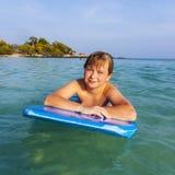 El muchacho adolescente goza el nadar en el océano Imagen de archivo