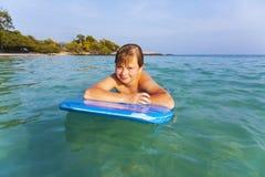 El muchacho adolescente goza el nadar en el océano Fotos de archivo libres de regalías