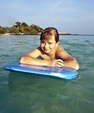 El muchacho adolescente goza el nadar en el océano Fotografía de archivo