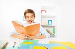 El muchacho adolescente hermoso leyó un libro que se sentaba en casa Imagen de archivo libre de regalías