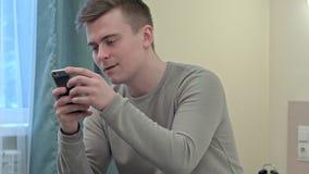 El muchacho adolescente hermoso risueñamente utiliza smartphone en su sitio en casa del estudiante Fotos de archivo libres de regalías
