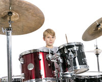 El muchacho adolescente joven juega los tambores en estudio contra el backgroun blanco Imagen de archivo