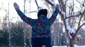 El muchacho adolescente lanza nieve en el bosque del invierno almacen de video