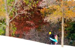 El muchacho adolescente lleva el trineo y la snowboard encima de una colina Nevado Imagen de archivo