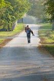 El muchacho adolescente lleva a la muchacha adolescente en el camino Imagenes de archivo