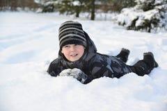 El muchacho adolescente miente en nieve en el bosque del invierno Imágenes de archivo libres de regalías