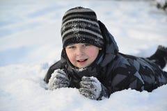 El muchacho adolescente miente en nieve en el bosque del invierno Fotografía de archivo libre de regalías