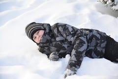 El muchacho adolescente miente en nieve en el bosque del invierno Fotos de archivo