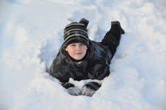 El muchacho adolescente miente en nieve en el bosque del invierno Fotos de archivo libres de regalías