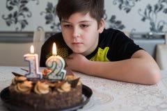 El muchacho adolescente mira cuidadosamente la torta con las velas en la duodécima fecha de nacimiento Foto de archivo libre de regalías