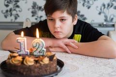 El muchacho adolescente mira cuidadosamente la torta con las velas en la duodécima fecha de nacimiento Fotos de archivo libres de regalías