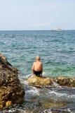 El muchacho adolescente mira el barco de mar Foto de archivo