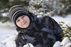 El muchacho adolescente mira hacia fuera de detrás árboles en bosque del invierno Fotos de archivo