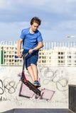 El muchacho adolescente monta su vespa en el parque del patín Fotos de archivo libres de regalías