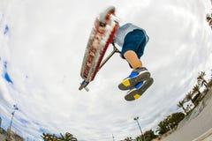 El muchacho adolescente monta su vespa en el parque del patín Imagen de archivo