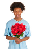 El muchacho adolescente negro está dando las flores Imagen de archivo