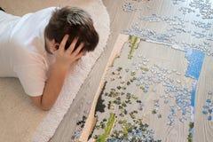 El muchacho adolescente recoge un rompecabezas que miente en la alfombra Foto de archivo libre de regalías