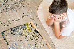 El muchacho adolescente recoge un rompecabezas que miente en la alfombra Fotos de archivo libres de regalías