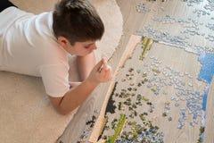 El muchacho adolescente recoge un rompecabezas que miente en la alfombra Imagenes de archivo