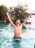 El muchacho adolescente salta en el agua Fotografía de archivo libre de regalías