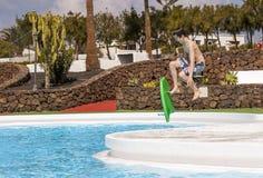 El muchacho adolescente salta en la piscina con su tablero de la boogie Imagen de archivo
