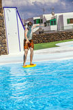 El muchacho adolescente salta en la piscina con su tablero de la boogie Fotos de archivo