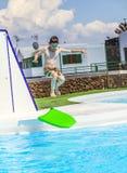 El muchacho adolescente salta en la piscina con su tablero de la boogie Fotografía de archivo