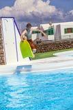 El muchacho adolescente salta en la piscina con su tablero de la boogie Fotografía de archivo libre de regalías