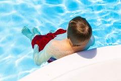 El muchacho adolescente se coloca en una piscina Fotografía de archivo libre de regalías