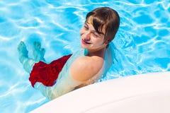 El muchacho adolescente se coloca en una piscina Imágenes de archivo libres de regalías