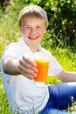 El muchacho adolescente se está sosteniendo de cristal con el zumo de naranja Imagen de archivo libre de regalías