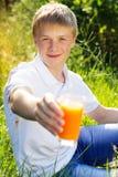 El muchacho adolescente se está sosteniendo de cristal con el zumo de naranja Imagen de archivo