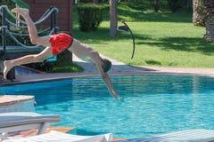 El muchacho adolescente se zambulle y nada en la piscina Foto de archivo libre de regalías