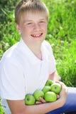 El muchacho adolescente sonriente lindo está sosteniendo manzanas verdes Imagen de archivo libre de regalías
