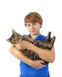 El muchacho adolescente sostiene su gato de gato atigrado en sus brazos Fotos de archivo libres de regalías