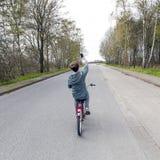 El muchacho adolescente toma un selfie mientras que completa un ciclo en el camino Imagen de archivo