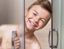 El muchacho adolescente toma una ducha en el cuarto de baño Fotografía de archivo