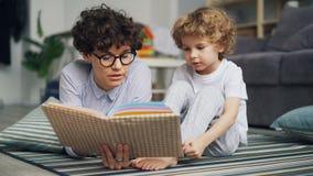 El muchacho adorable del niño está escuchando el hada-cuento mientras que la mamá está leyendo historia en casa almacen de video