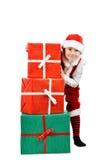 El muchacho adorable en la ropa de santa mira a escondidas hacia fuera detrás de las cajas de regalo grandes de la Navidad Fondo  Fotografía de archivo libre de regalías