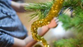 El muchacho adorna el árbol de navidad con los juguetes en casa almacen de video