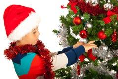 El muchacho adorna el árbol de navidad Imagen de archivo libre de regalías