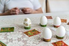 El muchacho adorna los huevos para Pascua con las etiquetas engomadas Imagen de archivo