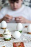 El muchacho adorna los huevos para Pascua con las etiquetas engomadas Fotos de archivo