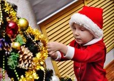 El muchacho adorna un árbol de navidad del Año Nuevo Imagen de archivo