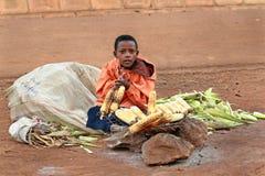 El muchacho africano vende la parrilla del maíz. Foto de archivo libre de regalías