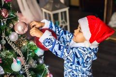 El muchacho afroamericano vistió el traje Santa Claus que adornaba un árbol de navidad fotos de archivo