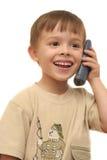 El muchacho agradable habla por el teléfono fotografía de archivo