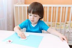 El muchacho agradable hace el muñeco de nieve del cojín de algodón Fotos de archivo libres de regalías