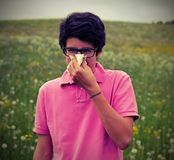 El muchacho alérgico con los vidrios y la camiseta rosada sopla su nariz Imagen de archivo