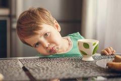 El muchacho alegre bebe la leche, come la tostada para el desayuno Foto de archivo
